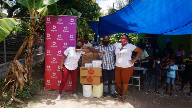 Jody-Ann Fearon Digicel Public Relations Executive presents gifts to Garnet and Camille Foster